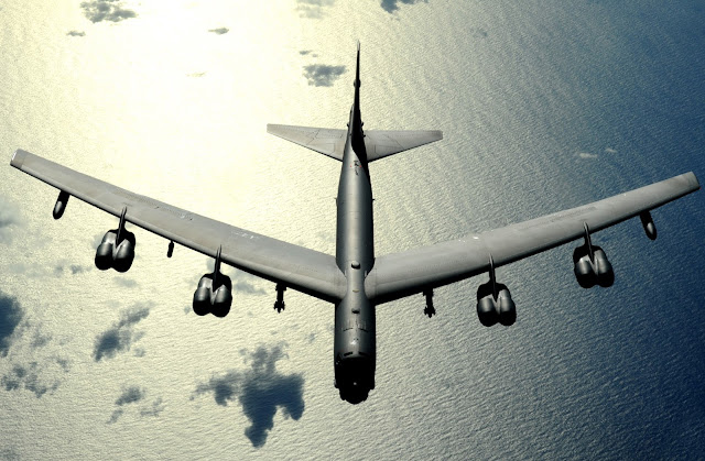 A B-52 Stratofortress flies high above the sea in the pacific.