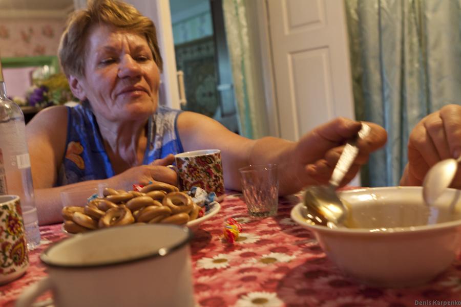 Женщина тянется с ложкой за только что собранным медом во время чаепития.
