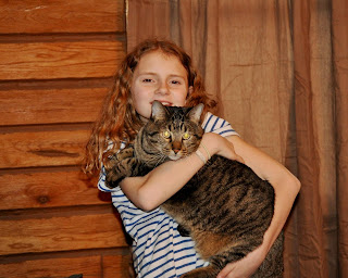 Nine year old girl holding a very large gray tabby cat in her arms