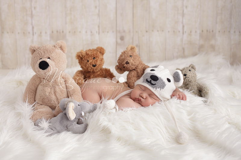 chubby little baby surrounded by teddy bears wearing a puppy dog ha