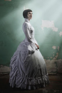 A Vulcan Victorian stands in a ray of sunlight with an opulent, full skirted gown
