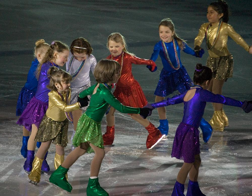 A group of young girls in costume at a figure skating event.