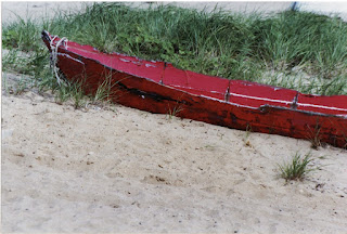 abandoned red boat by grass on the sand