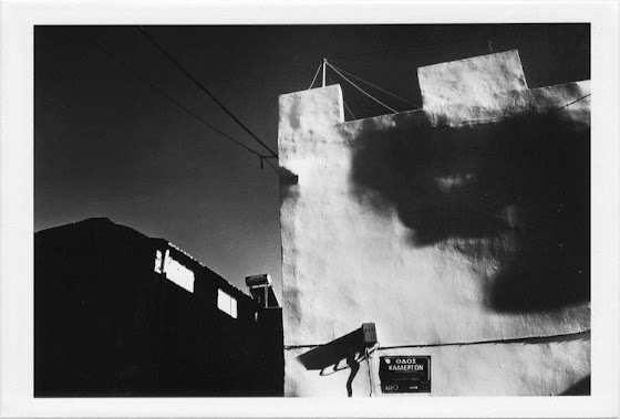 dirty photos - et - a black and white photo of face like shadow on wall in chania