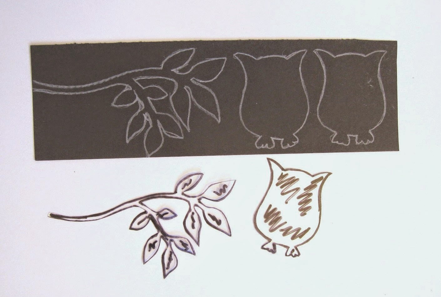 trozo plantilla de acetato transparente y cartulina negra con dibujo de búhos y rama