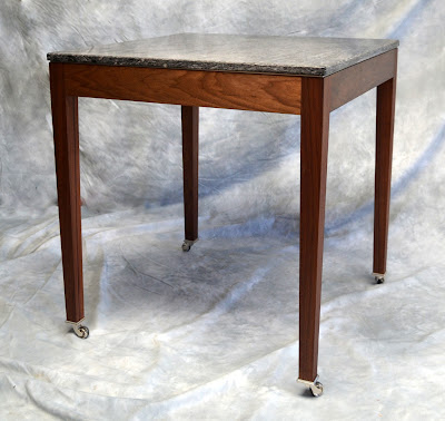 A small table on wheels made from american black walnut with a granite worktop.