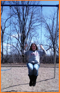 Happy on a swing set, no snow in evidence.