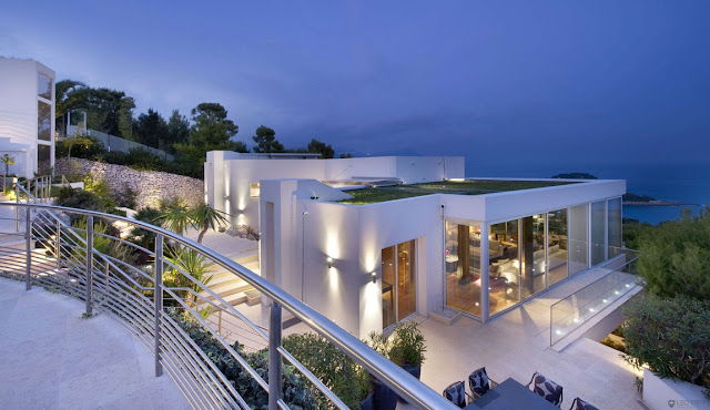 Modern villa looking out on the blue sea at the dusk