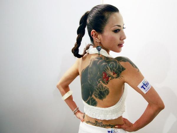 mujer asiatica posa de espaldas con vestido blanco, lleva tatuada en su espalda una pantera negra