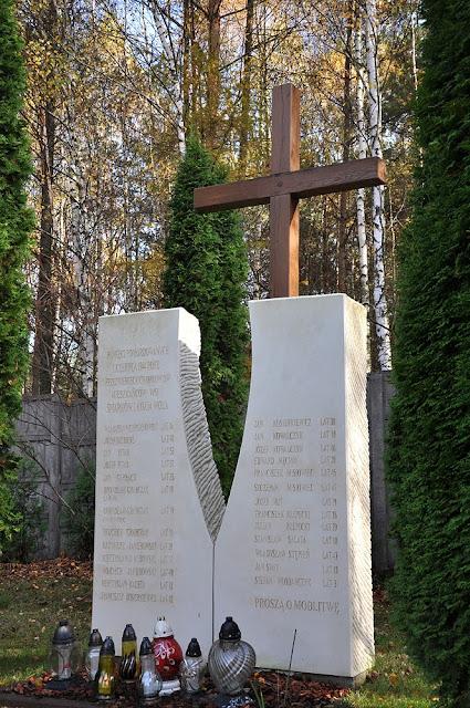 Nieświń, drewniany krzyż umiejscowiony od strony północnej kościoła p.w. św. Barbary. Po bokach znajdują się dwie kamienne tablice z nazwiskami pomordowanych. Krzyż drewniany postawiono na miejscu egzekucji w pobliżu kamieniołomu i zabudowań fabrycznych wówczas istniejących. Foto. KW.