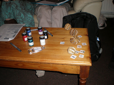 A table with paintpots and pens showing the layout of the bandit camp, dried seed pods showing undergrowth, and tokens indicating the characters.