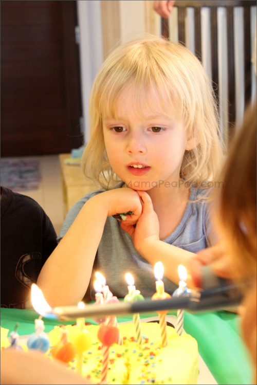 Four year old girl blowing out candles on her dinosaur birthday cake