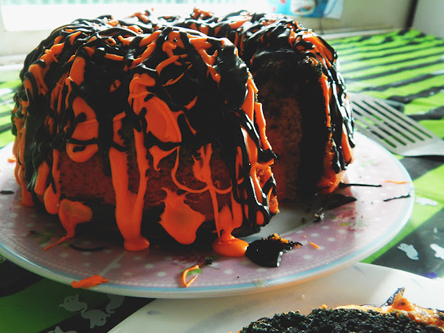 Orange and black frosting dripping over a bundt cake