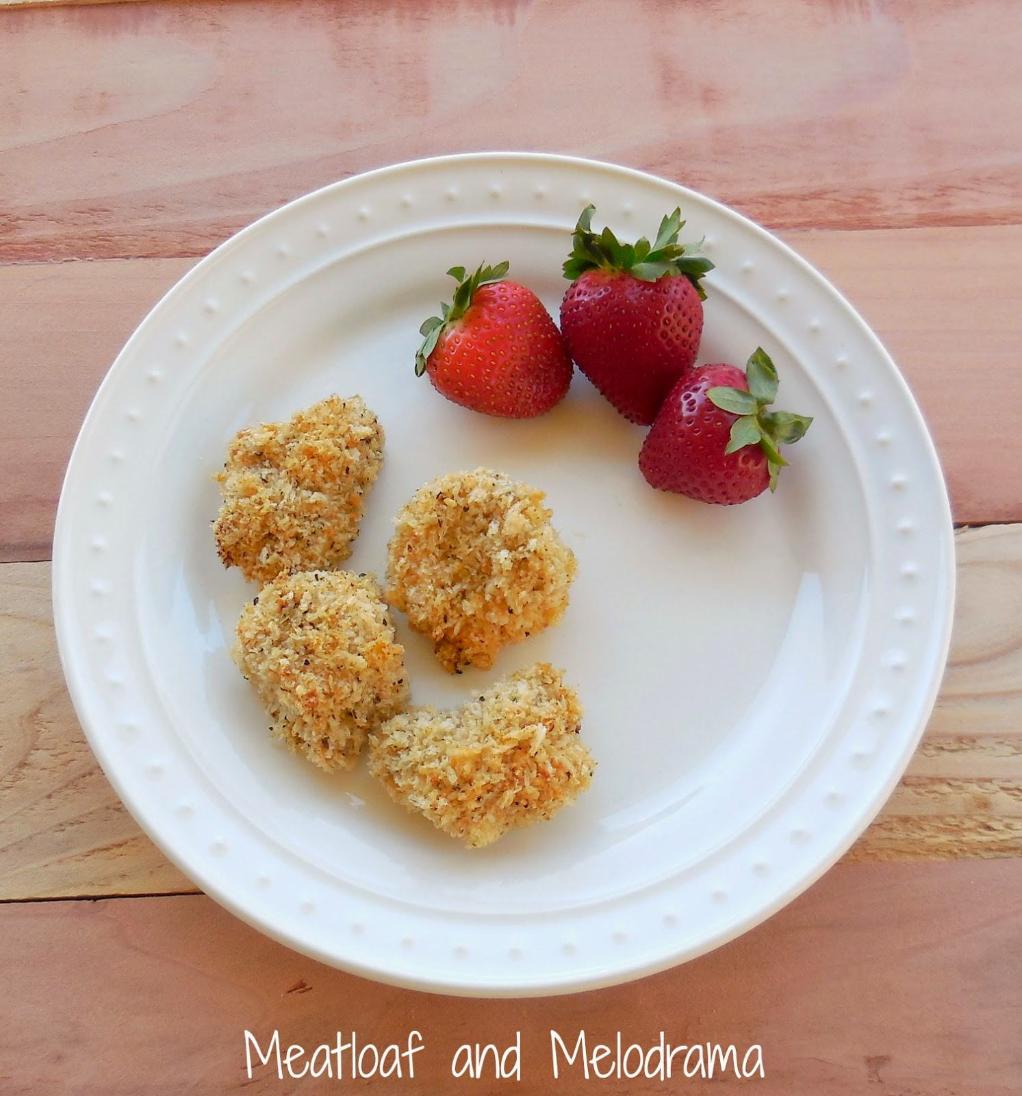 four panko crusted chicken nuggets and strawberries on plate