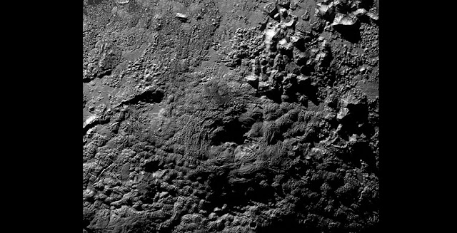 The informally named feature Wright Mons, located south of Sputnik Planum on Pluto, is an unusual feature that's about 100 miles (160 kilometers) wide and 13,000 feet (4 kilometers) high. It displays a summit depression (visible in the center of the image) that's approximately 35 miles (56 kilometers) across, with a distinctive hummocky texture on its sides. The rim of the summit depression also shows concentric fracturing. New Horizons scientists believe that this mountain and another, Piccard Mons, could have been formed by the 'cryovolcanic' eruption of ices from beneath Pluto's surface.   Credit: NASA/Johns Hopkins University Applied Physics Laboratory/Southwest Research Institute