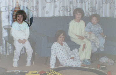 Four young girls, one highlighted, all in footed pajamas sitting on a couch