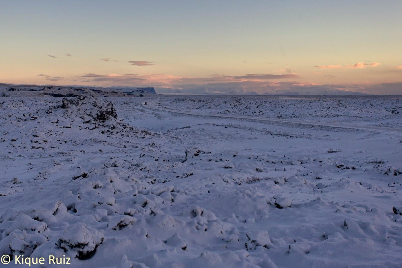 Nieve atravesada por una carretera y un coche a lo lejos, en Islandia