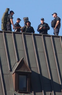 Holy shit! There are snipers up on the roof. With guns! And binoculars! What can they possibly be doing up there?