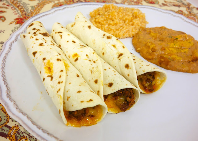 Baked Beef and Cheese Flautas - spicy taco meat and cheese baked in flour tortillas - great twist on taco night! Can assemble ahead of time and freeze for later.