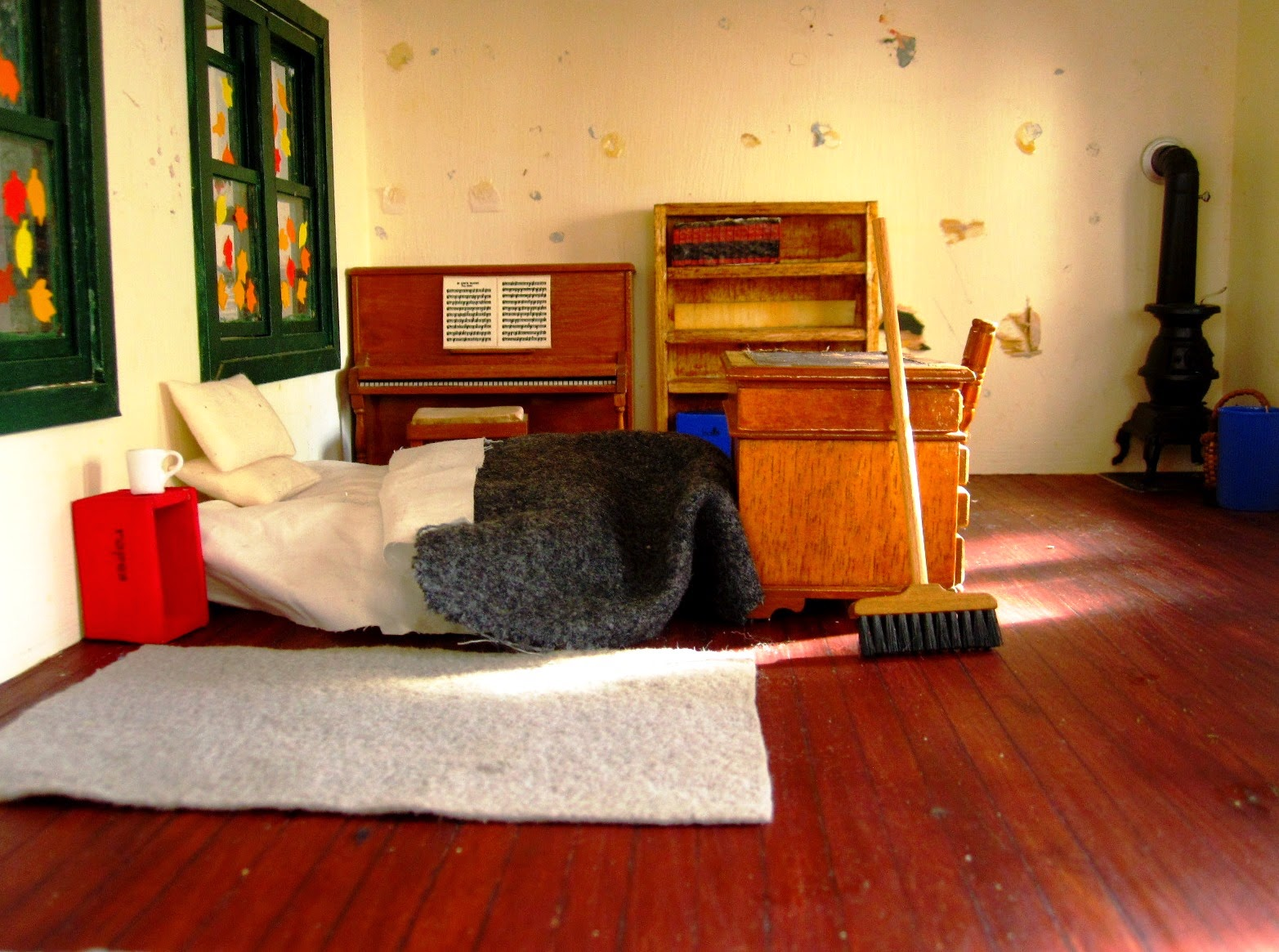 Miniature school house interior showing unmade bed on the floor with coffee mug next to it and a broom propped up at the end of it.