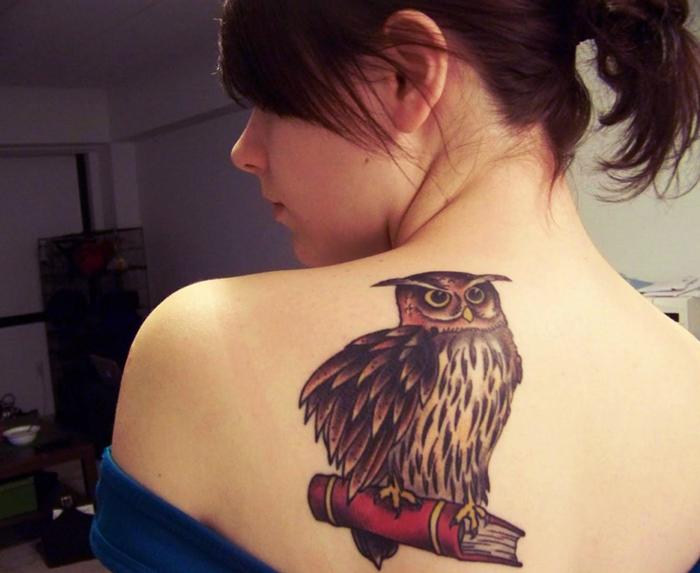chica con el pelo recogido nos muestra un tatuaje de buho en su omoplato