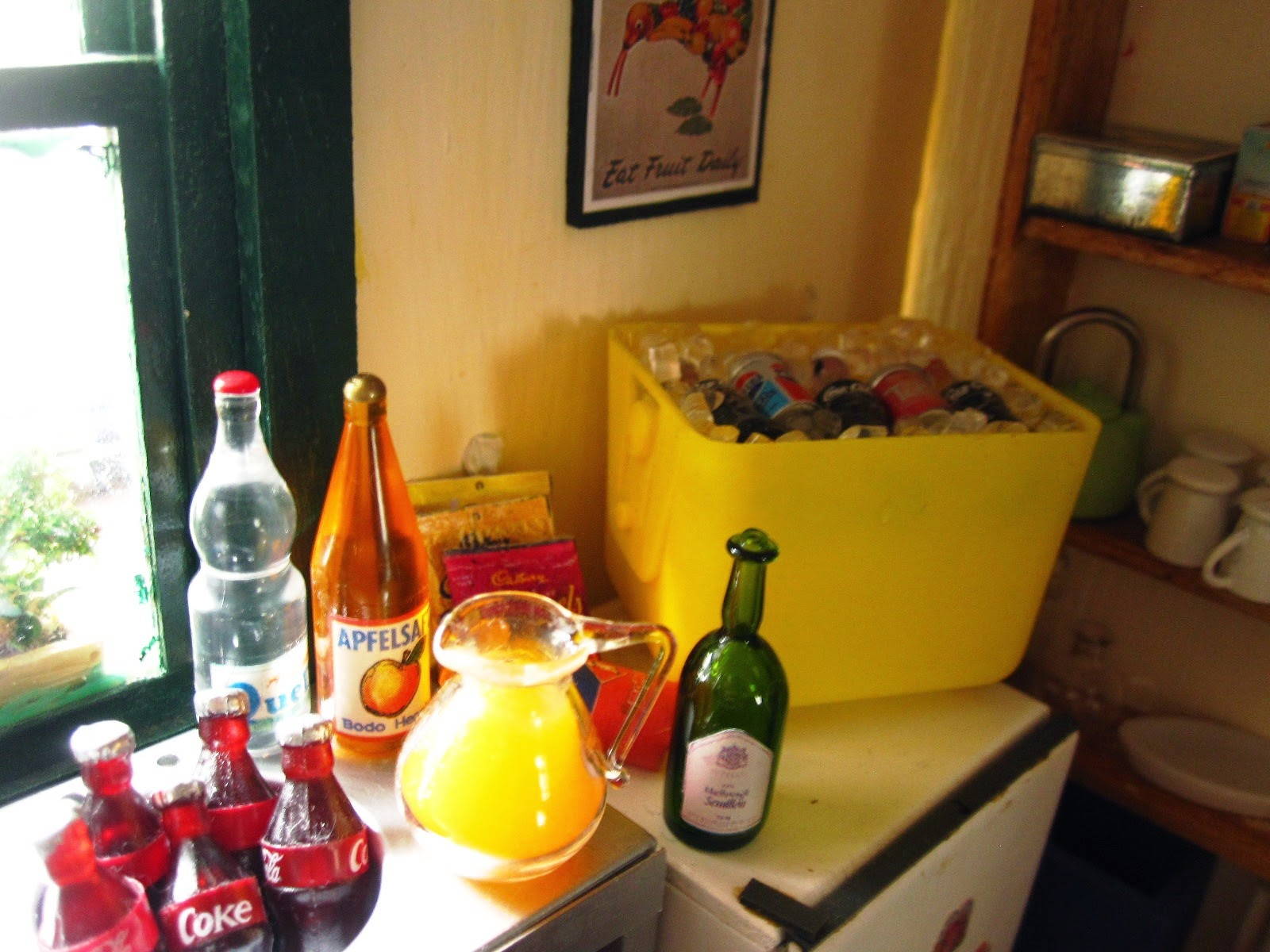Selection of miniature dolls' house non-alcoholic drinks arranged in a kitchen, ready for a party.