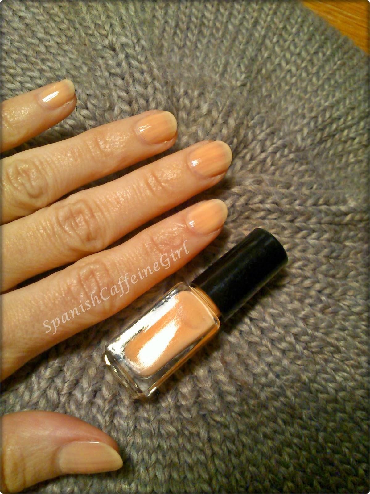 uñas con una capa de esmalte naranja muy claro