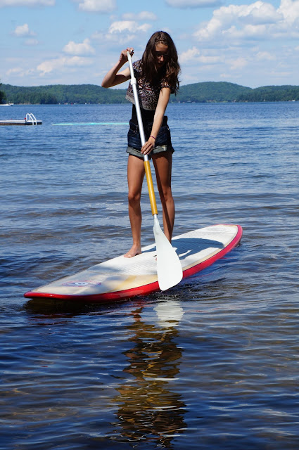 Stand up paddle boarding on a lake in Muskoka, while wearing Zara embellished top, American eagle over sized denim shorts