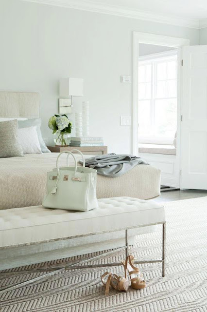 Pastel bedroom with an upholstered headboard, Chevron carpet with a Hermes Birkin on the white tufted bench