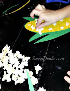 kid gluing popcorn onto the corn stalk craft