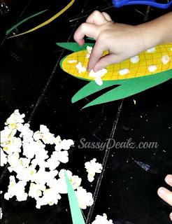 kid gluing popcorn onto the corn stalk craft