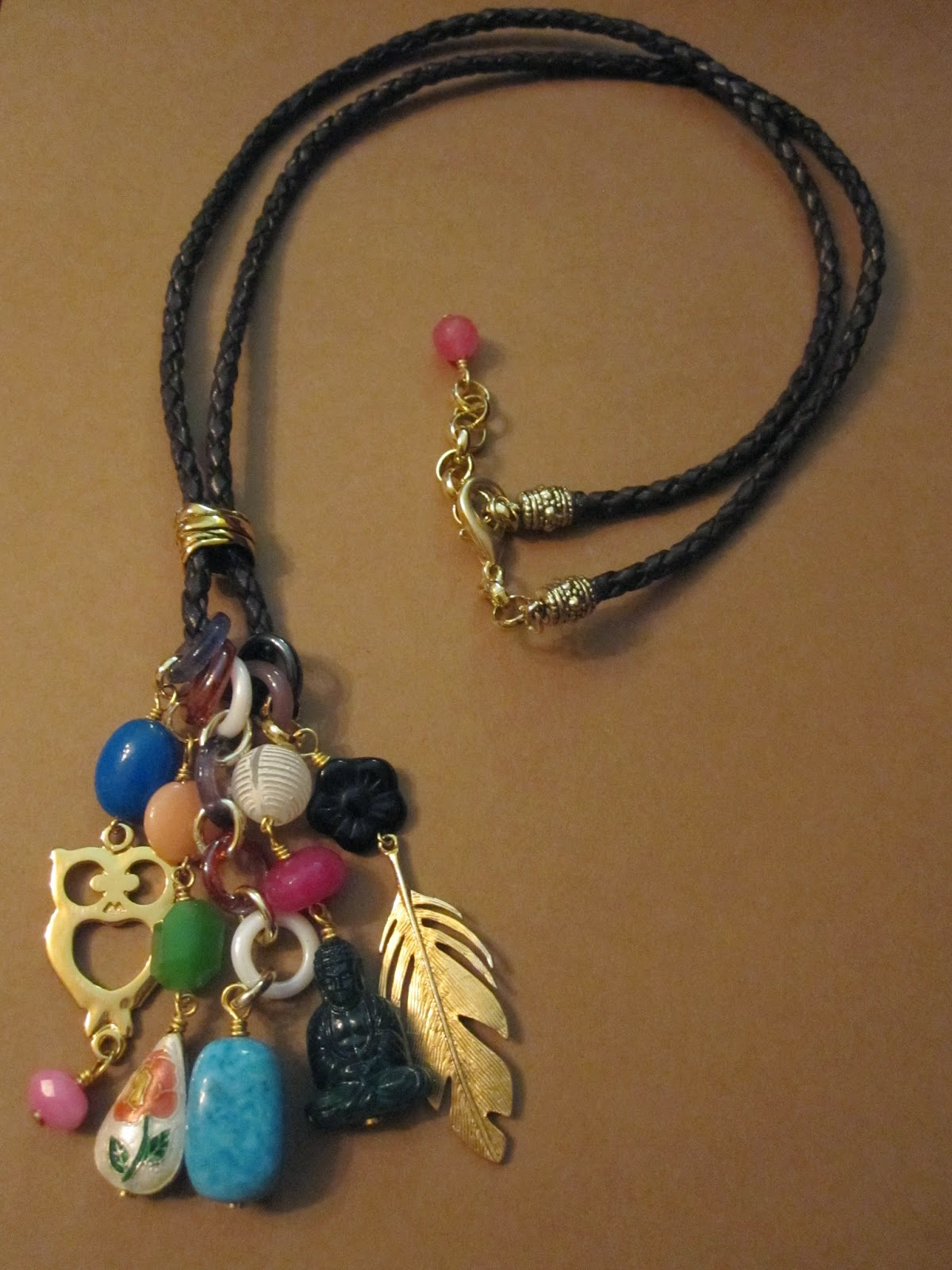 Collar largo en dorado con cordón de cuero trenzado en marrón oscuro, entrepieza, cierre y cadena dorada y diversos charms coloridos de metal,