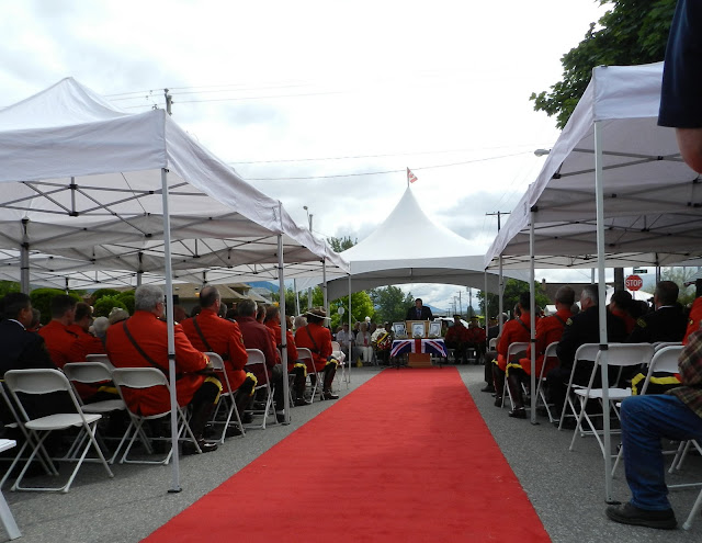 RCMP and guests sit under the tents and listen to the mayor's address