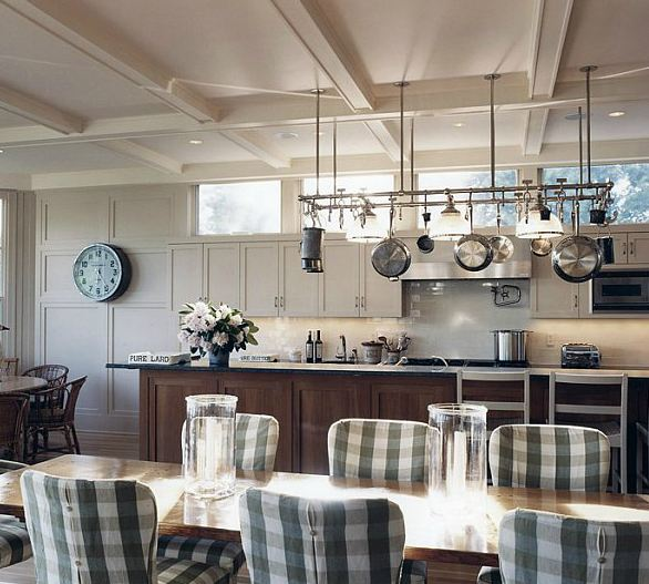 Dine in kitchen with hanging pot rack, white cabinets, a wood island with slab counter top, and a long wood table with gingham seat covers