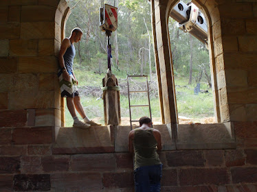 Lifting in one of the window stones and fixing it to the stone below with crane how they did it??