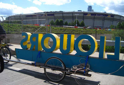 Bicycle trailer with 3D sign reading LIQUORS backwards, with the Minneapolis Metrodome in the background