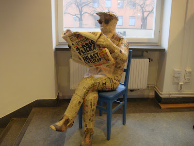 Sculpture of man reading newspaper, made from newspapers
