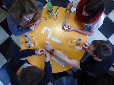 Vogelperspektive: An einem runden Tisch sitzen vier junge Leute und spielen Domino