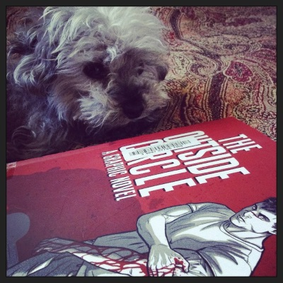A fuzzy grey poodle, Murchie, lays on a red tapestry comforter, head raised. In front of him is a trade paperback copy of The Outside Circle. Its red cover features a black and white line drawing of a young First Nations man with his right hand pressed over his left arm, which is bleeding. He also has a prominent scar cross his nose.