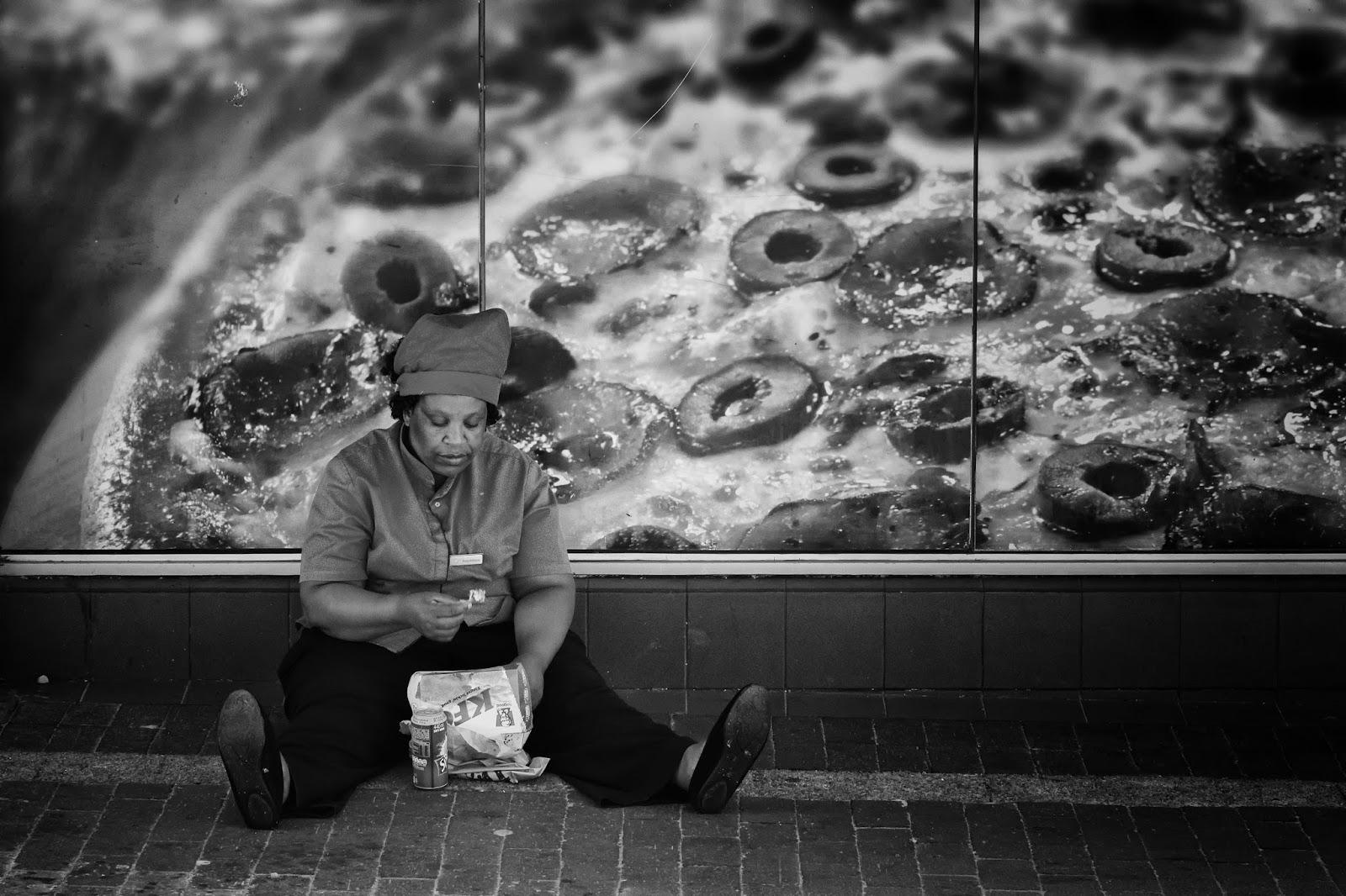 A woman eats junk food beneath a poster of junkfood.