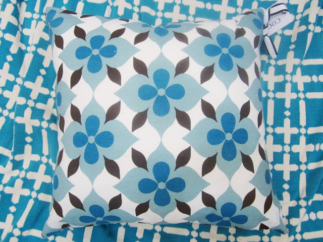 Nbaynadamas Coco's Flower cotton pillow in blue and brown on a peacock blue Nbaynadamas Plaid Solid Throw