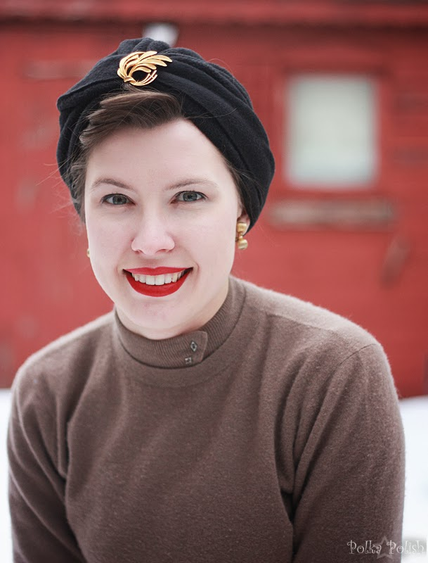 Smiling closeup, wearing a black fleece turban accessorized with a gold brooch outside in the snow