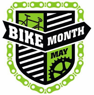 Heraldic shield divided into four quadrants, with the words 'Bike Month' superimposed across the upper portion of the shield. In the upper left quadrant, partial view of black bicycle against a green background. In the lower right, a black bicycle gear with the word 'May' against a green background. Black and white diagonal striping occupy the upper right and lower left quadrants and the entire shield image is outlined around its edge by a green bike-chain design.