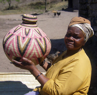Weaver from Zululand holds a Ukhamba basket she made.