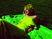 Rosie Huntington Whiteley wearing a  green dress and laying in the grass