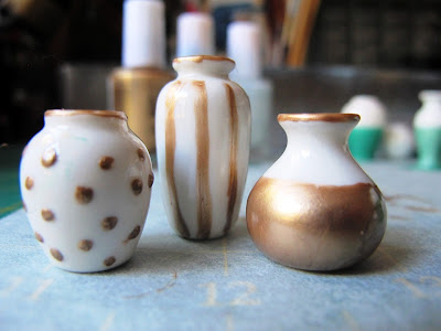 Three white dolls' house vases decorated with gold nail varnish: one spotted, one striped and one dipped, each with gold rims.