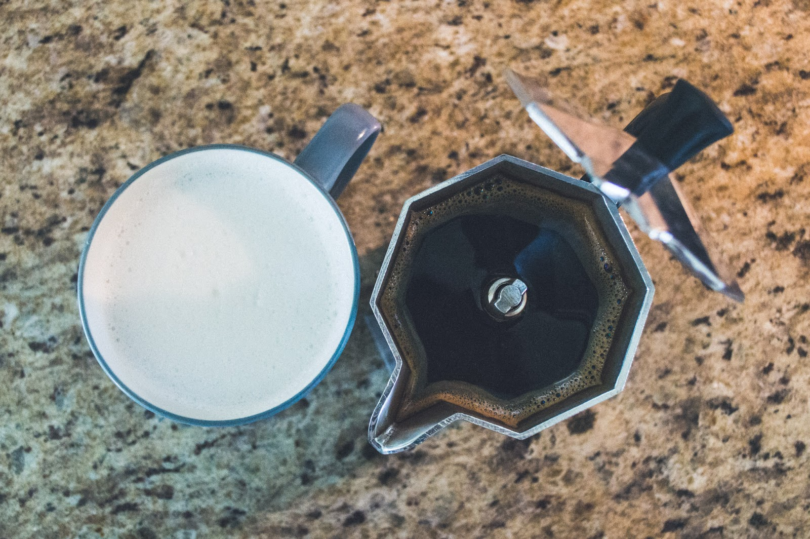 frothed almond milk in a mug and brewed coffee in moka pot