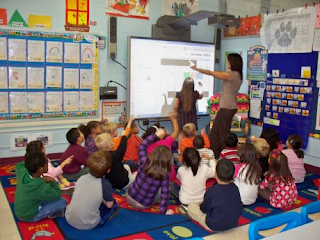 Kids and teacher using a SMARTboard in the classroom