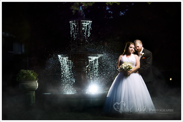 Bride and groom in front of fountain at night
