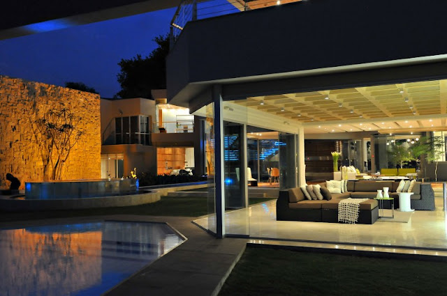 Photo of open living room by the pool at night